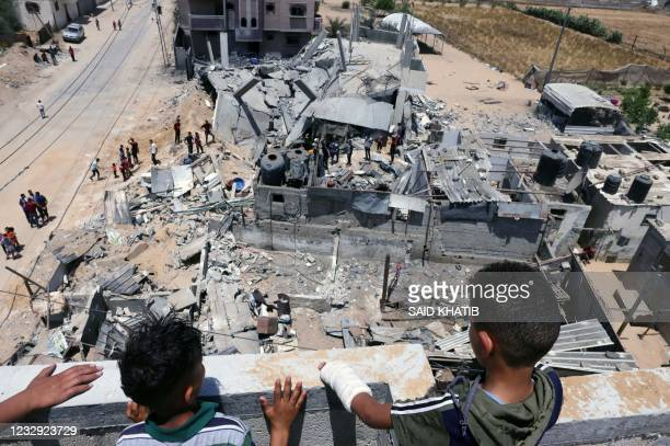 Palestinians inspect their house, after it was destroyed by an Israeli airstrike, in the city of Rafah, in the southern Gaza Strip on May 16, 2021. -...