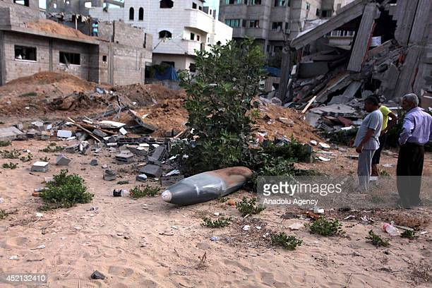 Palestinians inspect unexploded air missile near a house destroyed in air attacks staged by Israel army within the scope of 'Operation Protective...
