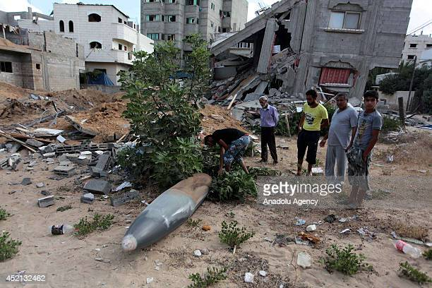 """Palestinians inspect unexploded air missile near a house destroyed in air attacks staged by Israel army within the scope of """"Operation Protective..."""