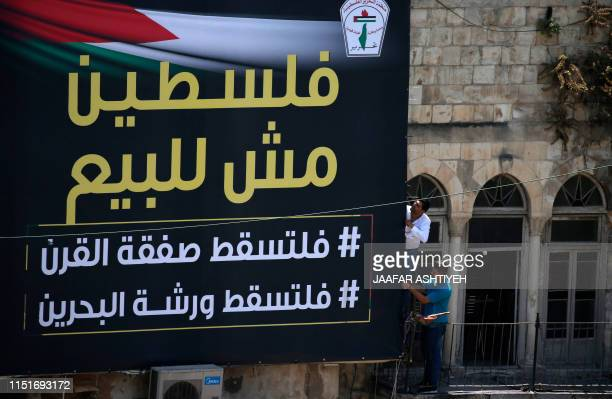 Palestinians install a banner reading Palestine is not for sale in the main square in the West Bank city of Nablus on 24 June in reference to a USled...