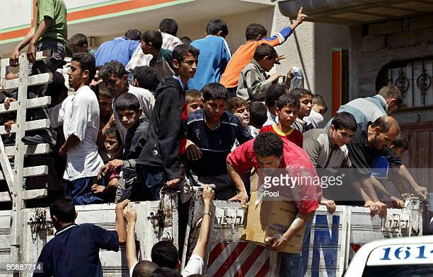 Palestinians jump on a United Nations truck to take food after several days of Israeli closure in the Tel alSultan neighborhood May 22 2004 in the...