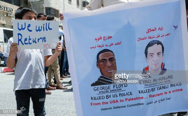 Palestinians lift banners protesting the killing of Iyad Hallak a disabled Palestinian man shot dead by Israeli police and that of George Floyd an...