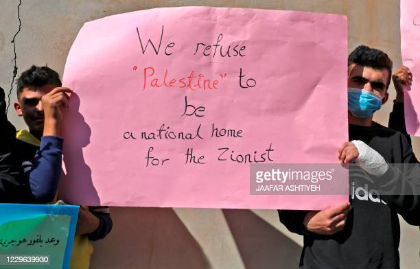 Palestinians lift placards as they protest outside a court building during the first session in a lawsuit filed by activists seeking compensation...
