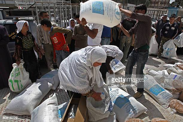 Palestinians living below the poverty line collect their bimonthly allocation of enriched flour oil salt sugar and chickpeas from a World Food...