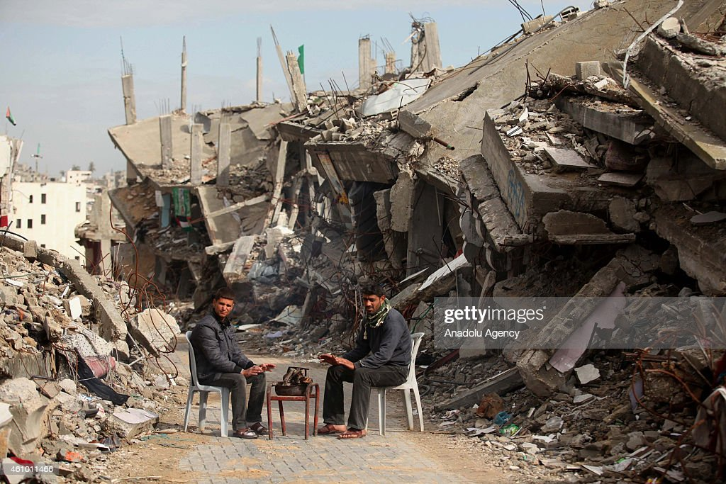 Palestinians living in heavy weather conditions amid the ruins of houses destroyed in Israeli attacks, get warm in Gaza's Shejaiya district on January 4, 2015.