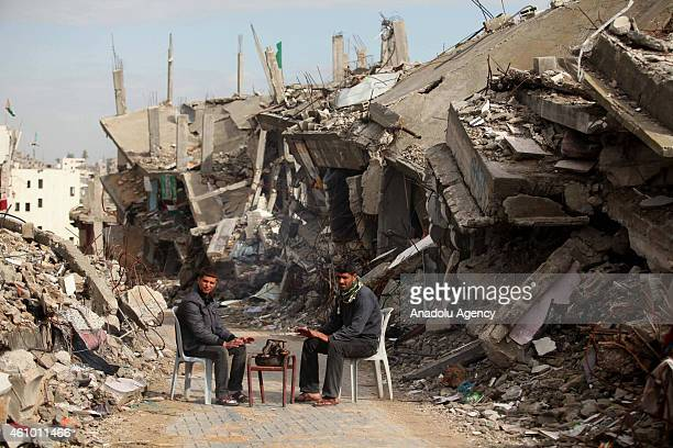 Palestinians living in heavy weather conditions amid the ruins of houses destroyed in Israeli attacks get warm in Gaza's Shejaiya district on January...