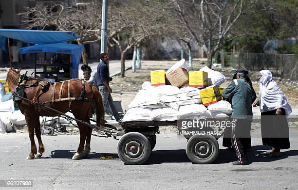 Palestinians load food supplies on a horsepulled cart outside a United Nations Relief and Works Agency aid distribution centre in Gaza City on April...