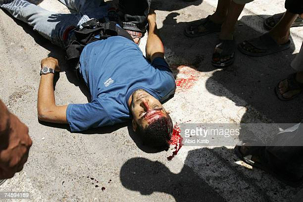 Palestinians look a the body of a member of the Preventative Security Force loyal to the Palestinian president Mahmoud Abbas on June 14 2007 in Gaza...