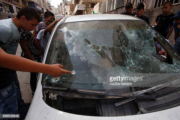 Palestinians look at a damaged car belonging to a Palestinian man who was killed by Israeli security forces after he attempted to ram his vehicle...