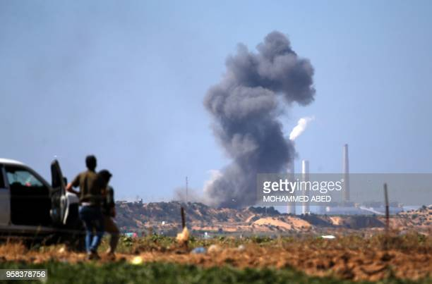 TOPSHOT Palestinians look at smoke billowing from the site of an Israeli air strike on a Hamas' military site in Beit Lahia near the border between...