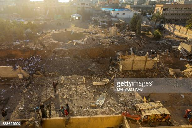 TOPSHOT Palestinians look at the damage at a Hamas military facility early on December 9 in the aftermath of an Israeli air strike in Beit Lahia in...