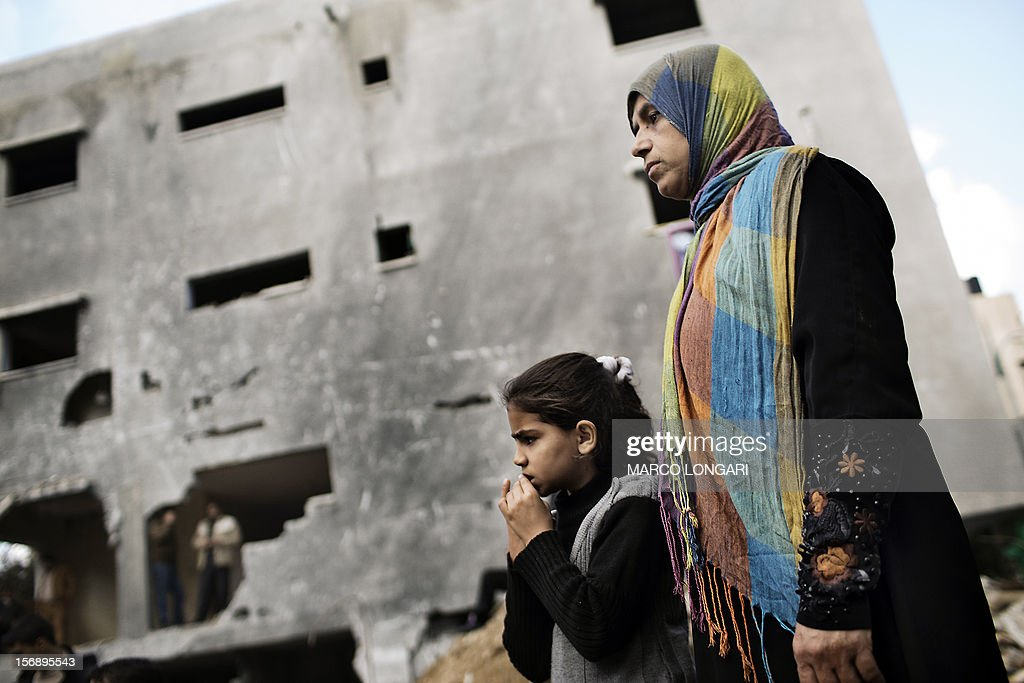 Palestinians look on during a ceremony for the young victims of the al-Dallu family, killed by an Israeli airstrike in Gaza City on November 24, 2012. An Israeli missile struck a three-story building in Gaza City on November 18, killing several members of the al-Dallu family - five of them children - and two of their neighbours.