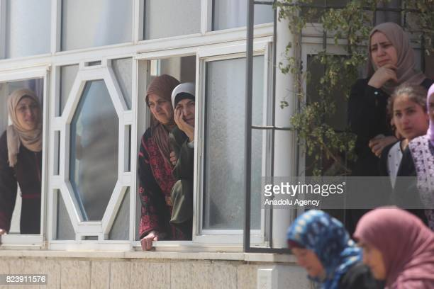 Palestinians look on through a window during the funeral ceremony of Muhammad Fathi Kanaan who was killed by Israeli security forces during a...