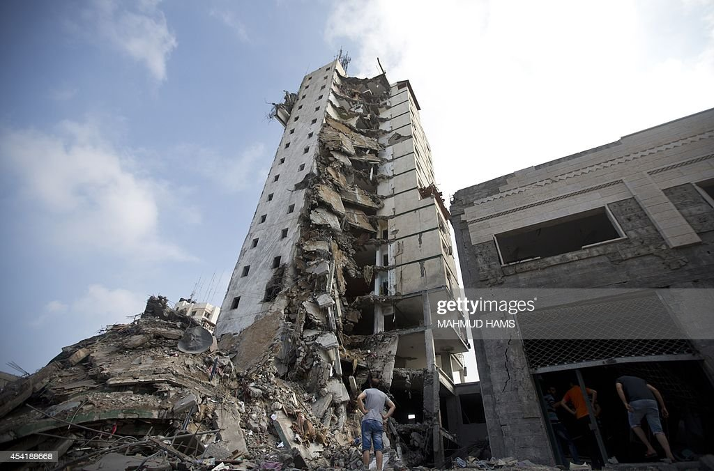 Palestinians look up at the remains of an Italian apartment block that was destroyed by an Israeli air strike overnight in Gaza City on August 26, 2014. An Israeli air raid in Gaza killed two Palestinians as Israel pursued its campaign to stop rocket fire by Hamas militants from the enclave, medics said.