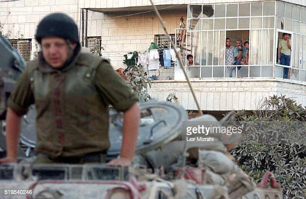 Palestinians looks from the windows at Israelis soldier next to Yasser Arafat's compound in Ramallah, September 22, 2002. The Israeli army pressed...