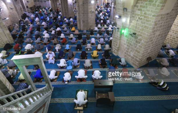 Palestinians maintaining social distancing attend the last Friday prayer of the fasting month of Ramadan on May 22 at al-Omari mosque in Gaza City,...