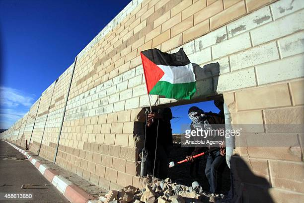 Palestinians make a hole in Israeli West Bank barrier separating Israel and the West Bank and plant Palestinian flag one day before the 25th...