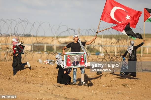 Palestinians man hold Turkish flag and Turkish President Recep Tayyip Erdogan's portrait to celebrate his presidential election success as they...