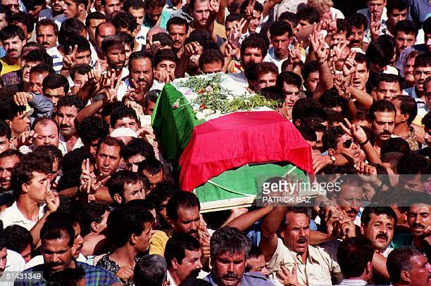 Palestinians march through the streets of Gaza City carrying the coffin of PLO senior member Assad Saftawi during his funeral 22 October 1993 Saftawi...