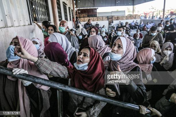 Palestinians, mask-clad due to the COVID-19 coronavirus pandemic, wait to cross to the Egyptian side of Rafah border crossing in the southern Gaza...