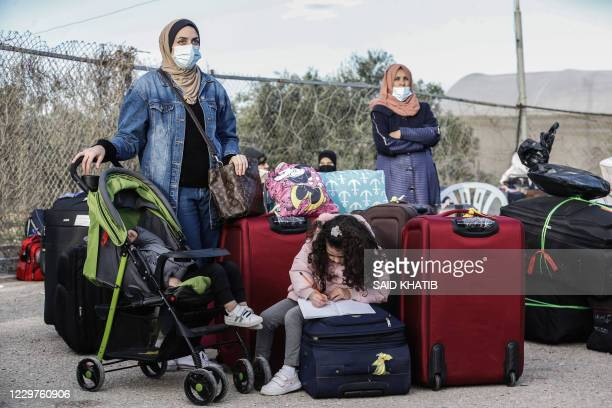 Palestinians maskclad due to the COVID19 coronavirus pandemic wait to cross into Egypt through the Rafah border crossing in the southern Gaza Strip...