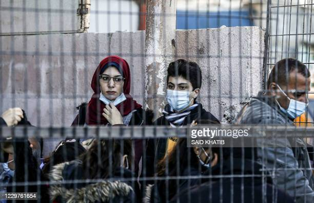 Palestinians maskclad due to the COVID19 coronavirus pandemic wait to cross onto the Egyptian side at the Rafah border crossing between the Gaza...