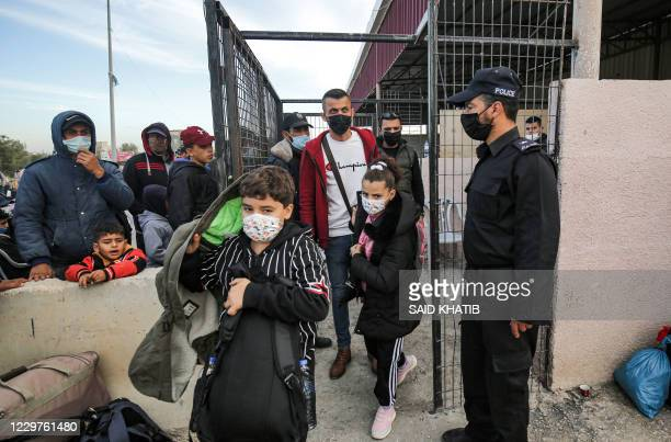 Palestinians maskclad due to the COVID19 coronavirus pandemic walk at the Rafah border crossing between the Gaza Strip and Egypt before crossing onto...