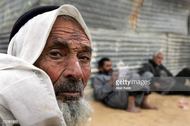 Palestinians men sit outside a building March 06, 2005 in the Rafah Refugee Camp in the Gaza Strip near the Egyptian border. Palestinians who had...
