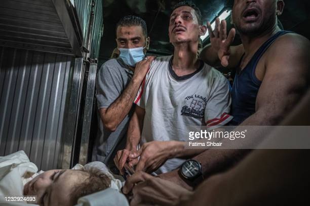 Palestinians mourn their relatives who were killed during an Israeli raid on Gaza City on May 16, 2021 in Gaza City, Gaza. More than 140 people in...