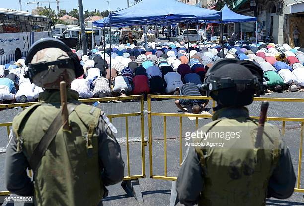 Palestinians not allowed to enter to the AlAqsa Mosque for Friday prayer perform their prayers outside the mosque as Israeli police set up barricade...