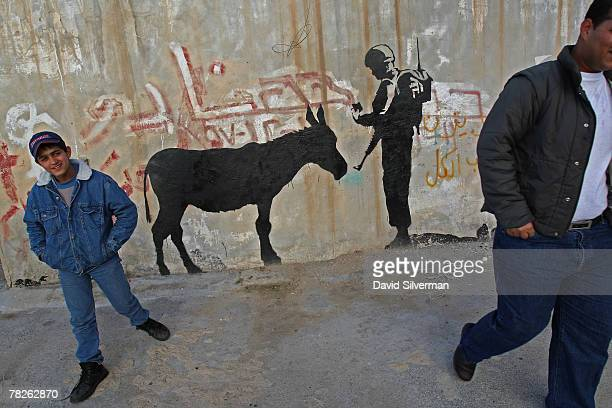 Palestinians pass a wall painting by elusive British graffiti artist Banksy December 5 2007 on a shop wall in the biblical city of Bethlehem in the...