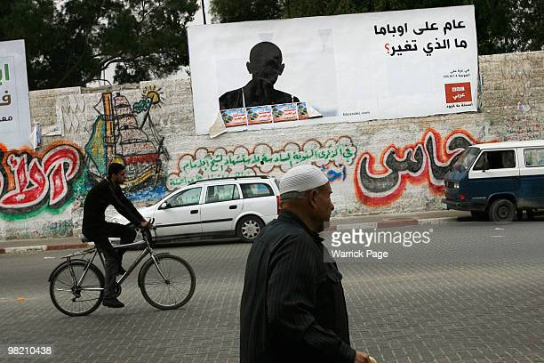 """Palestinians pass an Arabic news-radio billboard featuring the shilouette of US President, Barack Obama, asking, """"One year in office, has anything..."""