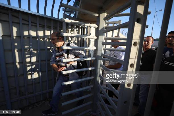 Palestinians pass the door one by one as they wait in a queue after Israeli forces got under control the check point following a Palestinian woman...