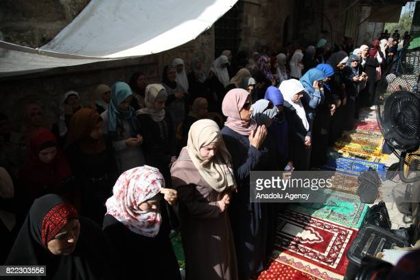 Palestinians perform afternoon prayer in front of AlAqsa Mosque Compound to stage a demonstration after Israeli authorities decided to remove metal...