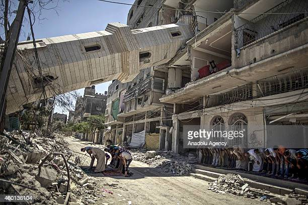 Palestinians perform Friday prayer at the El Suusi Mosque destroyed in an Israeli assault a week ago in AlShati Refugee camp Gaza on August 08 2014...