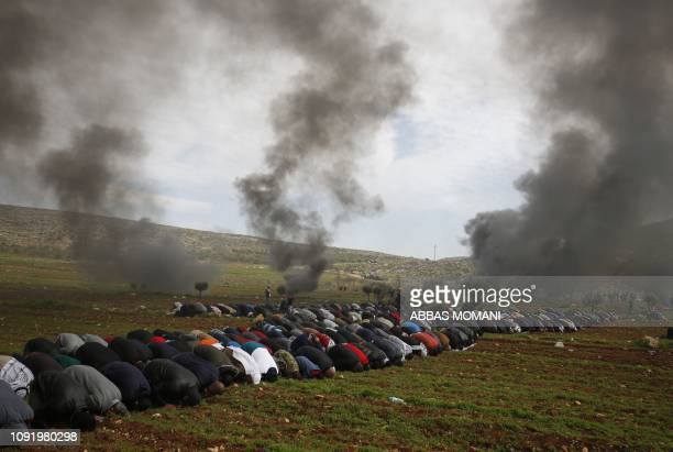 TOPSHOT Palestinians perform Friday prayers as smoke rises from burning tires during a protest against Jewish settlements in alMughayyir village near...