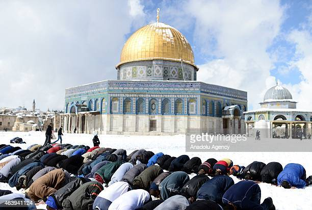 Palestinians perform Friday prayers at snow covered yard of Al Aqsa Mosque for Friday prayer after snowfall hit region on February 20 2015