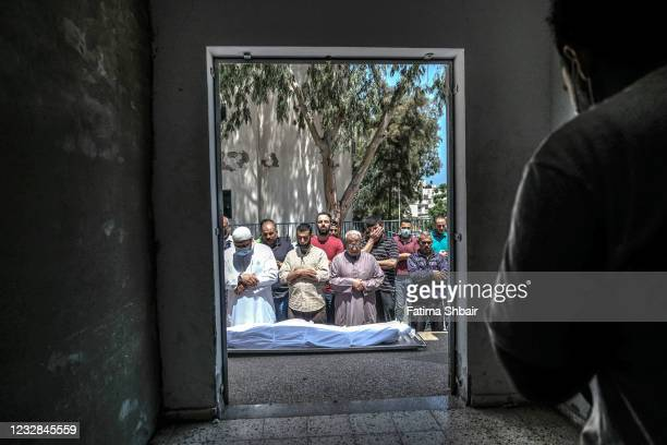 Palestinians perform funeral prayers for a Palestinian martyr, who was killed during an air strike in central Gaza City on May 12, 2021 in Gaza City,...