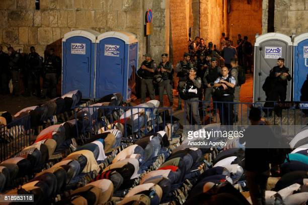 Palestinians perform night prayer in front of the new security metal detectors outside one of the main entrances to the AlAqsa mosque refusing to...