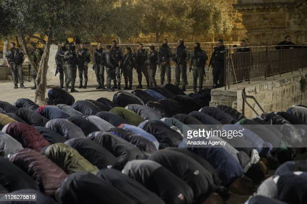 Palestinians perform prayer in front of AlRahma Gate of AlAqsa Mosque Compound as Israeli security forces stand guard behind them after AlRahma Gate...