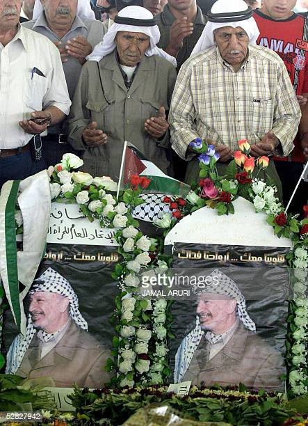Palestinians pray at the grave of late leader Yasser Arafat in the West Bank city of Ramallah 15 May 2005 as they mark the Nakba day 57 years on from...