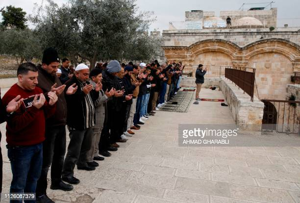 Palestinians pray in front of the small door of the Golden Gate at alAqsa Mosque compound in the Old City of Jerusalem on February 20 2019