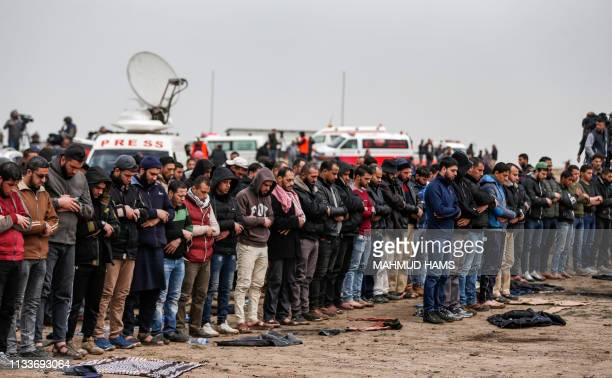 Palestinians pray together during a demonstration near the border with Israel in Malaka east of Gaza City on March 30 as Palestinians mark the first...
