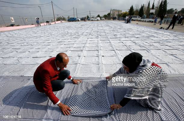 "Palestinians prepare a 1400 square metre keffiyeh , nicknamed ""Arafatian"" after the late Palestinian leader Yasser Arafat, as they launch the process..."