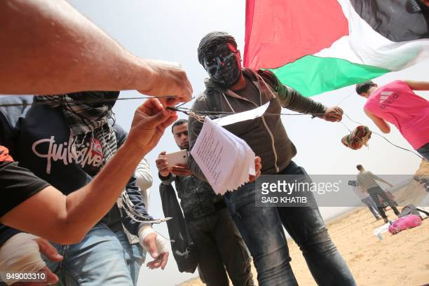 Palestinians prepare a kite carrying a fire bomb and leaflets before trying to fly it over the border fence with Israel in Rafah in southern Gaza...