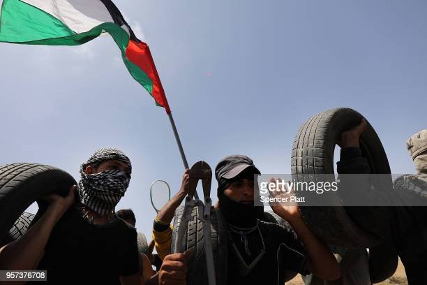 Palestinians prepare to burn tires near the border fence with Israel as mass demonstrations at the fence continue on May 11 2018 in Gaza City Gaza...