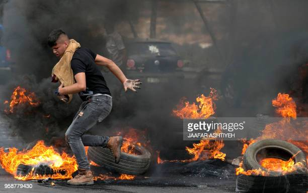 Palestinians protesters are seen during clashes with Israeli security forces after a protest marking Nakba or catastrophe commemorating the more than...