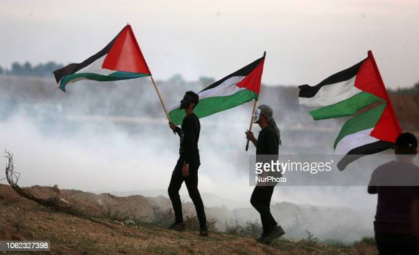 Palestinians protesters carry national flags as they gather during a protest east of Gaza City near the Israeli border on November 16 2018 The Gaza...
