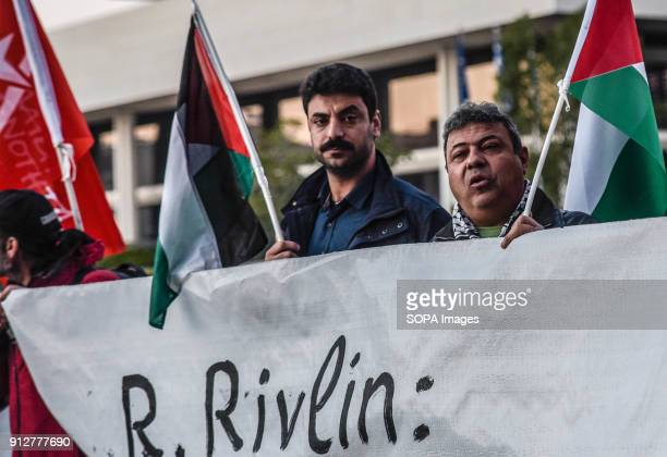Palestinians protesters hold a banner that reads 'Not Welcome' against the visit of Israeli President Reuven Rivlin in Athens