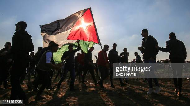 Palestinians protesters march with a Palestinian flag during a demonstration at the border fence with Israel east of Gaza City on March 22 2019